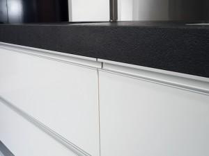 Gavetas en blanco brillo con tirador metálico integrado que contrastan con la encimera de piedra negra