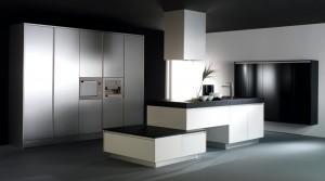 Diseño de cocina con isla de muebles blancos y encimera negra, completada con columnas en acero y semicolumnas en negro