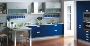 Frentes de gavetas en azul brillo que contrastan con la vitrina en aluminio y cristal