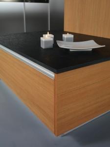 Encimera de piedra negra que contrasta con el acero de las columnas y la madera de los muebles bajos